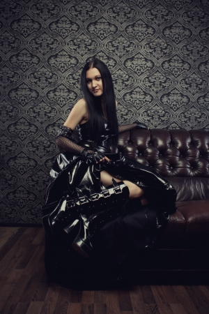 latex girl: Portrait of gothic girl in black latex dress sitting on a sofa