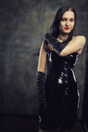 Seductive gothic girl in black latex dress over grunge background photo