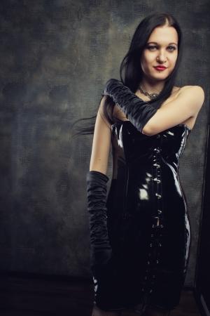 herrin: Verführerische gothic girl in schwarzen Latex-Kleid über Grunge-Hintergrund