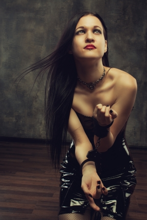 masochism: Portrait of sexy gothic girl in handcuffs standing on knees Stock Photo