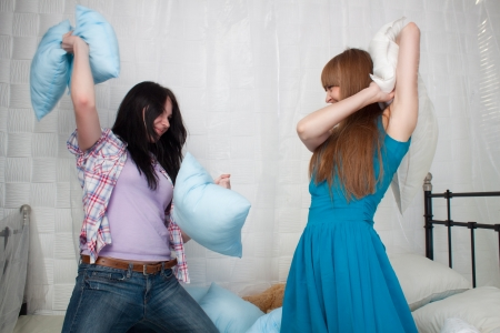 Two girls having a pillow fight at home  photo