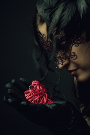 Old-fashioned young lady in mask holding heart in her hands Stock Photo