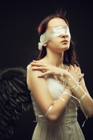 Cute angel with bandage on her eyes posing over black background photo