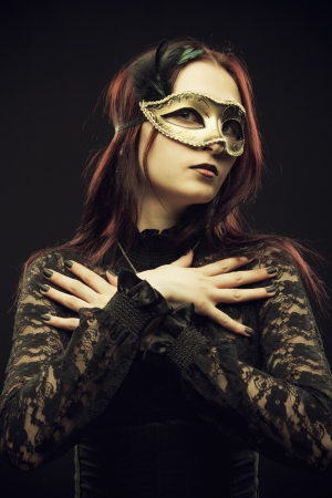 Seductive girl in mask posing over black background Stock Photo - 20572052
