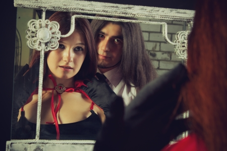 Pretty young  lady looking  in mirror. Brutal long-haired man stands behind her. photo