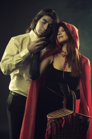 Brutal long-haired man holding hand of Red Riding Hood over dark background photo