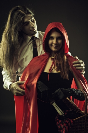 cloak and dagger: Red Riding Hodd with basket and Bad Wolf over dark background