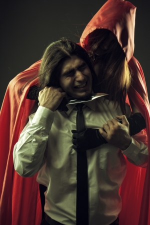 Red Riding Hood holding knife to Bad Wolf's throat photo