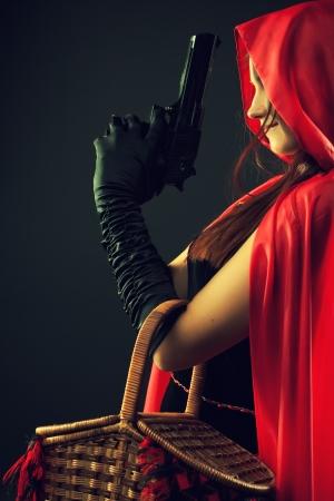 暗い背景上のポーズの銃を持つかわいい赤ずきんちゃん 写真素材