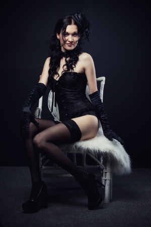 stoking: Seductive old-fashioned girl in black sits on white chair Stock Photo