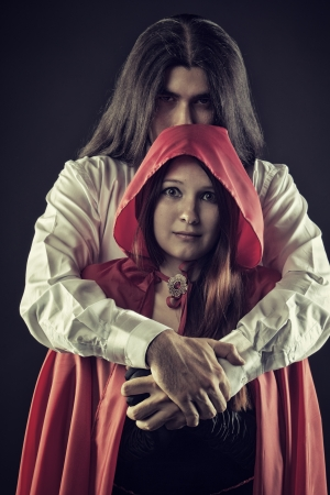 Sinister Bad Wolf embraces misirable Red Riding Hood over dark background photo