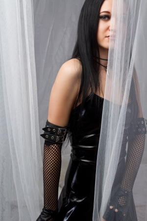 Gothic beautiful woman behind a curtain  photo