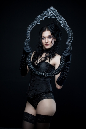 Attractive gothic girl in black corset and panties with frame over dark background photo