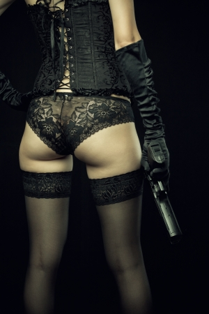 Seductive girl holding gun over black background. Rear view.  Stock Photo