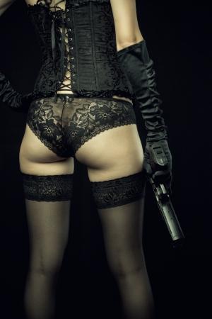 Seductive girl holding gun over black background. Rear view. Stock Photo - 21001584