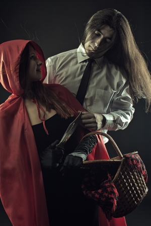 cloak and dagger: Red Riding Hood with basket and Bad Wolf over dark background Stock Photo