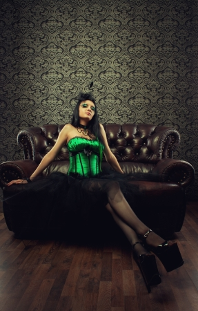 Pretty old-fashioned lady in green corset sits on a divan