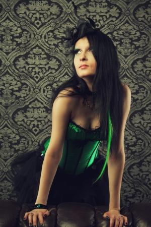 divan: Hada atractiva en cors� verde se encuentra detr�s de un sof�