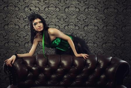 divan: H�bsche Fee im gr�nen Korsett steht hinter einem Diwan