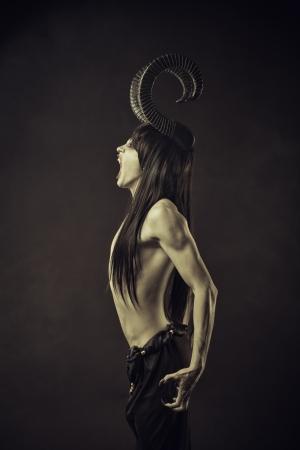Angry horned devil posing over dark background