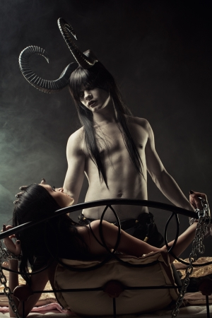 Horned dark-haired devil and chained innocence gothic girl in bed Stock Photo
