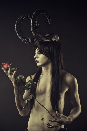 Horned devil with red roses over black background Stock Photo - 21410517