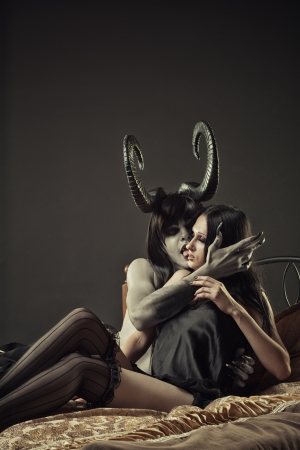 Horned pale devil and cute gothic girl in bed