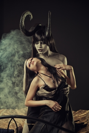 Seductive gothic girl and horned demon in bed