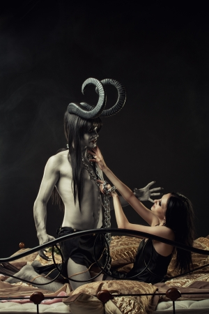 Chained devil and cute gothic girl in bed photo