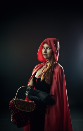 Pretty Little Red Riding Hood over dark background photo