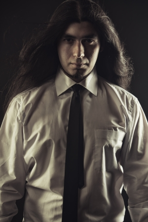 Portrait of handsome young man with long hair over black background. Low key.