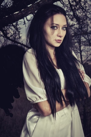 Portrait of beautiful sad girl with wings standing in the forest photo