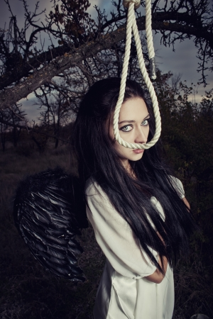 Sad angel with black wings and gallows photo