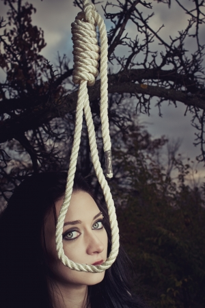 Pretty girl with gallows in the forest. photo