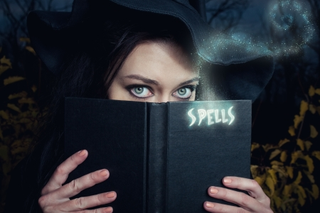 witch face: Pretty witch  with spells book in the forest Stock Photo