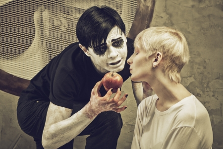 insane insanity: Crazy guy with apple and sad girl in a cell of an lunatic asylum Stock Photo