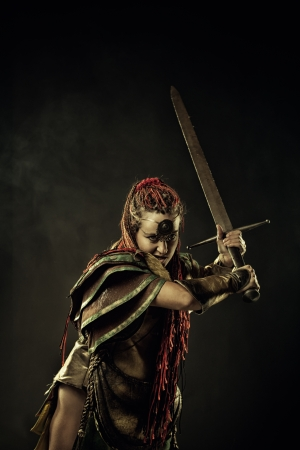 Powerful furious amazon with two-handed sword over dark background 写真素材