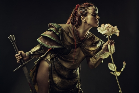 Brutal barbarian warrior with sword smelling the rose over dark background Stock Photo