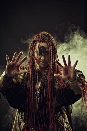 fanatical: Wicked shaman with bloody hands in smoke Stock Photo