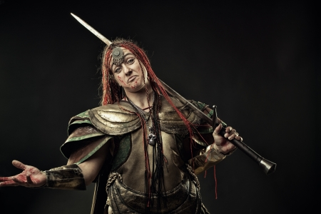 Brutal bloody woman warrior in armour over dark background photo