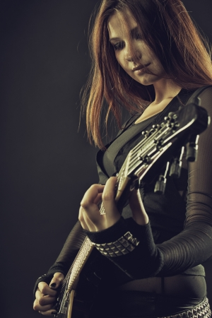 Pretty young woman with electric guitar posing over dark background 写真素材