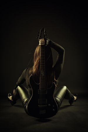 Pretty rocker sitting on the floor with guitar   写真素材