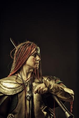 Pretty mercenary with sword posing over dark background