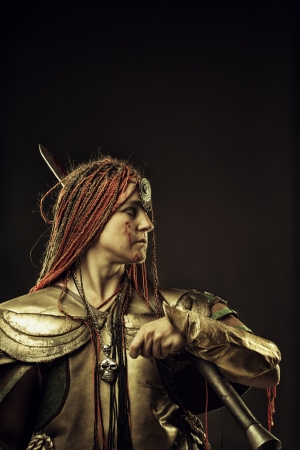 Pretty mercenary with sword posing over dark background photo