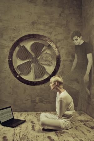 psychopath: Sad girl in straitjacketsitting in a cell of an asylum. Hallucination stands behind her.