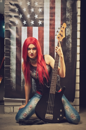 bass guitar women: Red head rock and roll star sitting on the floor