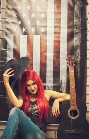 Redhead girl with cowboy hat and broken acoustic guitar over american flag photo