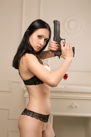 Seductive spy with gun posing in underwear  photo