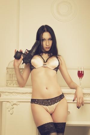 Seductive girl with gun posing in underwear  photo