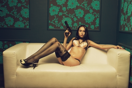 Seductive spy sitting on a sofa with gun photo
